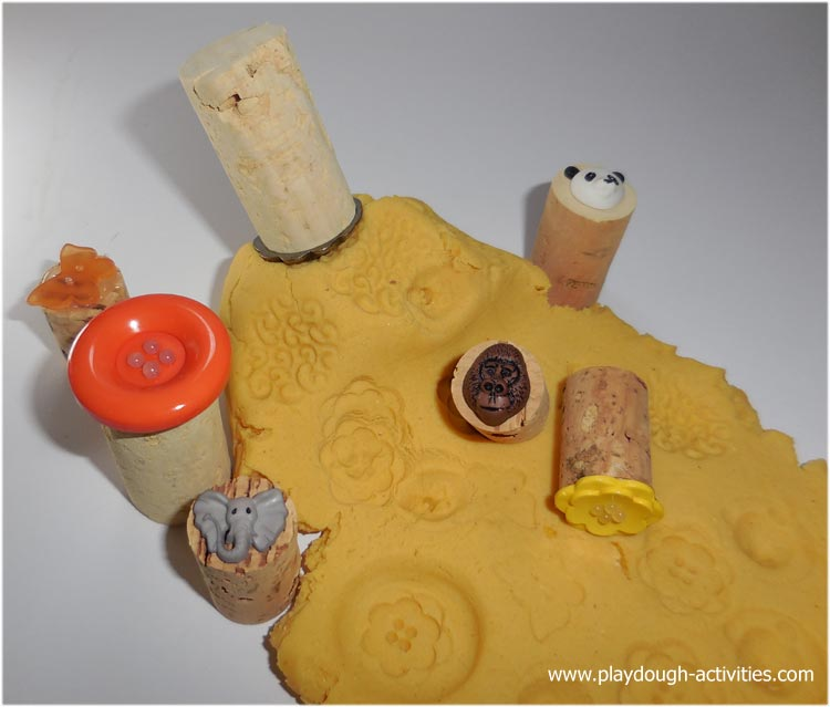 Recycled button playdough stampers creating patterns on the surface
